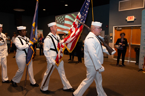 Color guard bringing American flag to front stage at Veteran's Expo