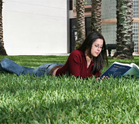 girl on lawn reading book